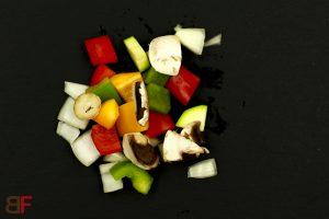 Knoblauchbutter in der Pfanne erhitzen. Zwiebel, Zucchini, Champignons und alle Paprikastücke dazugeben und unter Rühren anrösten.