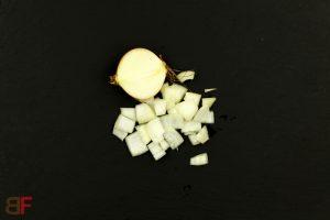 Rapsöl in einer Pfanne erhitzen, Zwiebeln dazugeben und unter Rühren ca. 2 Minuten anrösten.