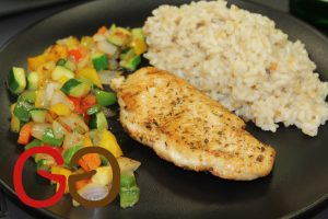 Den Reis auf die Teller mit dem Fleisch und dem Gemüse anrichten.