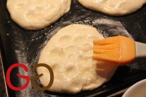 Das Ei mit 100 g Wasser verquirlen und auf die Teigstücke streichen. Darauf je nach persönlicher Vorliebe Sesam und schwarzer Kümmel streuen.