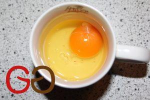 Das Ei aufschlagen und in eine Tasse geben.
