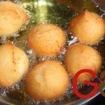 Einen Esslöffel etwa zur Hälfte mit Teig füllen und mit einem zweiten Esslöffel durch mehrmaliges Abstreifen ineinander in eine kugelartige Form bringen. Diese im heißen Fett schwimmend ausbacken.