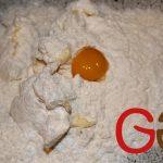 Zutaten für den Mürbteigboden (Mehl, Puderzucker, Margarine, Ei) auf die Arbeitsplatte geben.